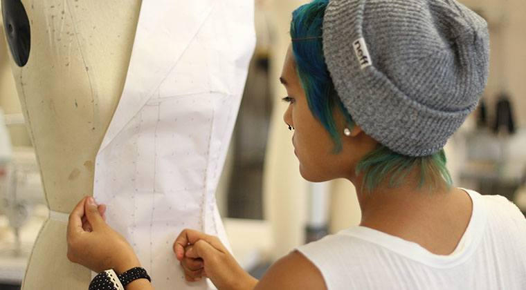 A fashion student putting her pattern onto a mannequin