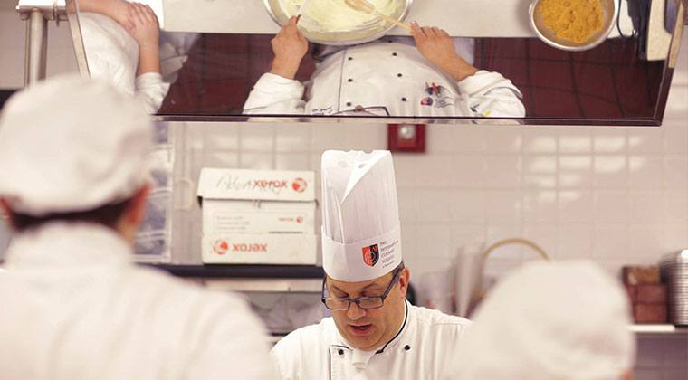 Here, a chef instructor shows baking and pastry students how to prepare buttercream icing.