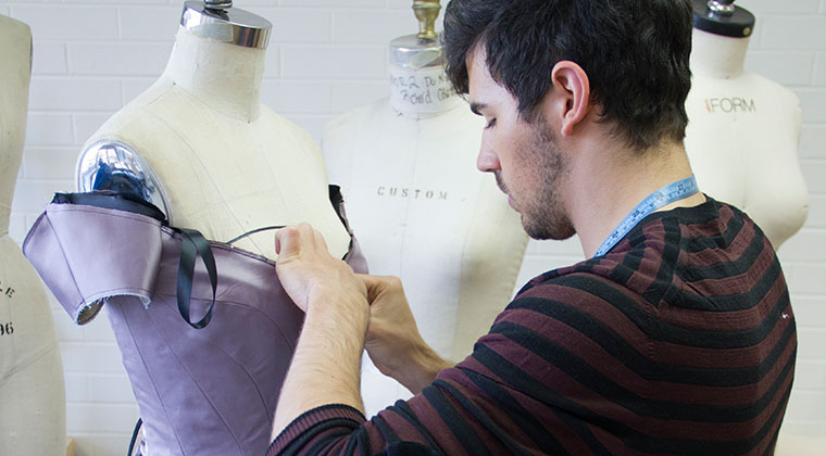 A fashion design student works on a dress at the River North Point campus.