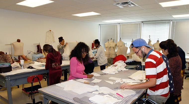 A fashion design class works on projects inside of the sewing lab.