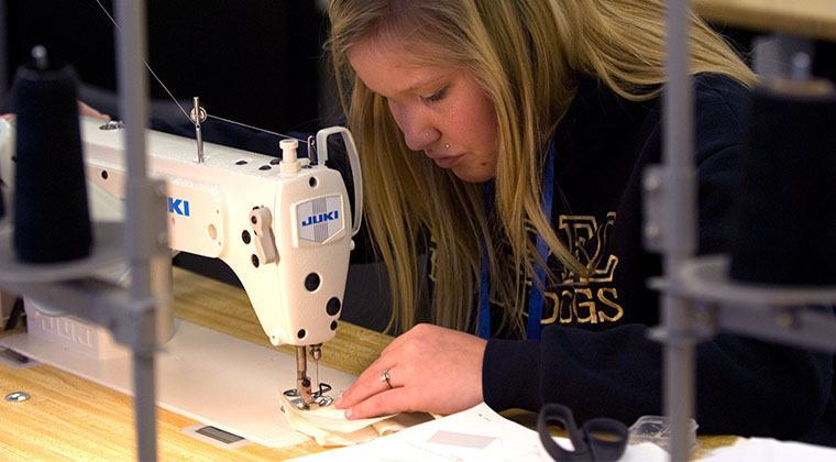 A fashion design student is using an industrial Juki sewing machine to stitch her garment.
