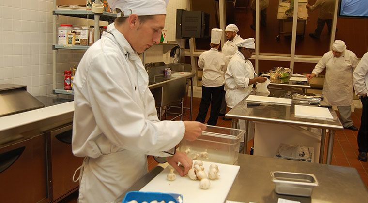 A culinary student is prepping for an assignment in the a la carte kitchen.