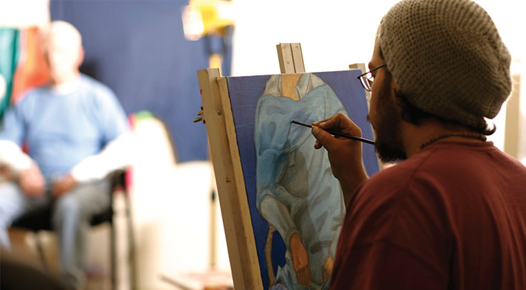 A Visual Arts student works from a live model in this painting course.