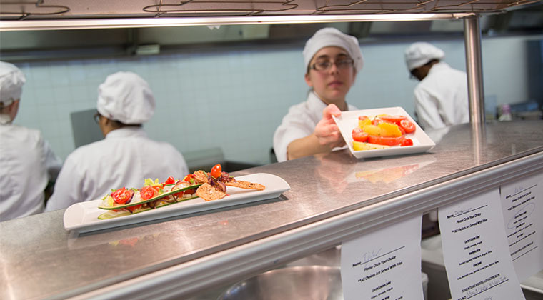 A student prepares a dish-to-order in the á la carte kitchen of Culinaire Restaurant.