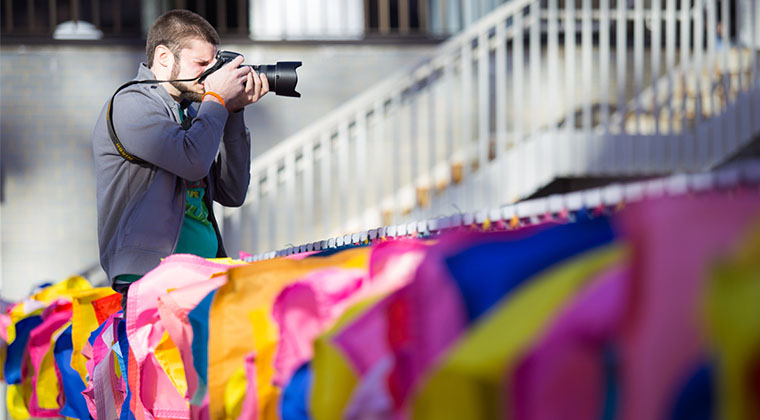 A Photography student takes his shot amid fluttering flags.