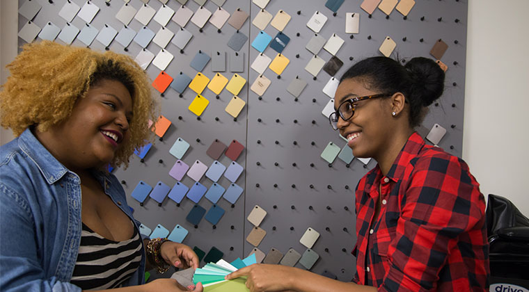Two Interior Design students discuss colors options for finishes.