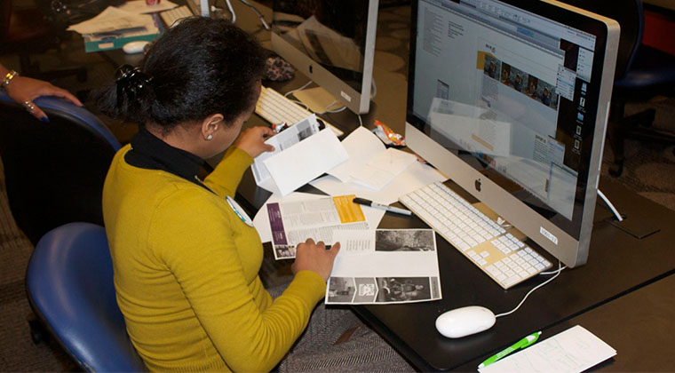 A Graphic Design student makes changes to the digital files of a brochure.