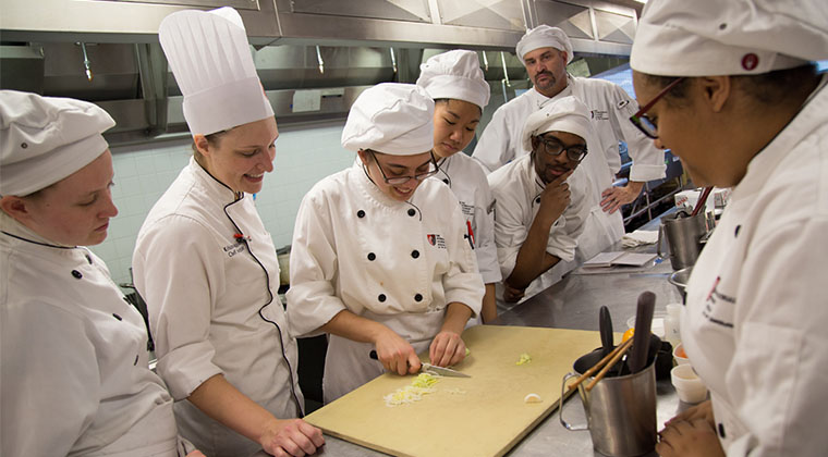 A Culinary student demonstrates her knife skills for the chef instructor while her fellow students observe.